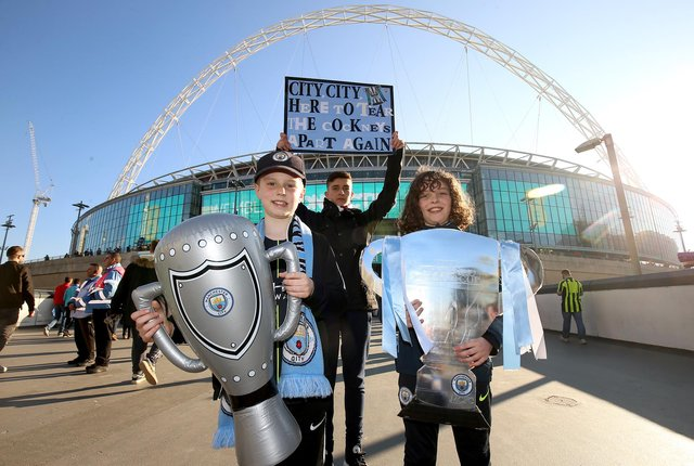 Manchester City fans hold up replicas of the Carabao Cup trophy prior to the beginning of the 2019 Carabao Cup Final at Wembley Stadium.