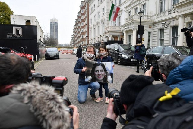 Richard Ratcliffe, husband of British-Iranian aid worker Nazanin Zaghari-Ratcliffe jailed in Tehran since 2016, and his daughter Gabriella, hold a picture of Nazanin as they protest outside of the Iranian Embassy in London on March 8, 2021 (Photo by BEN STANSALL/AFP via Getty Images)