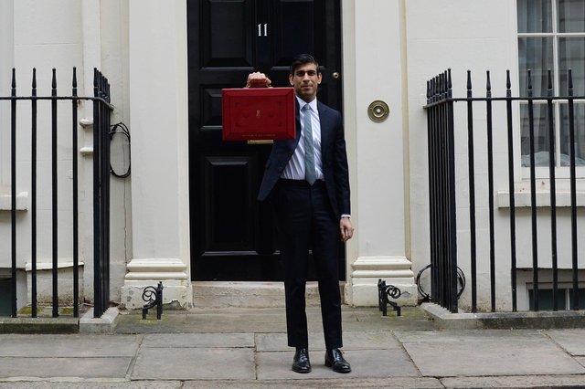 Sunak stands with the Budget Box, in Downing Street, back in March before pledging to extend the furlough scheme.