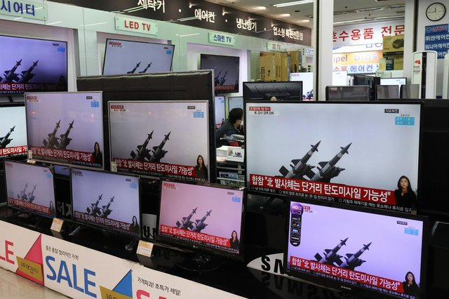 TV screens showing a news report about North Korea's missiles